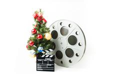 Christmas tree with big cinema reel and movie clapperboard - stock photo