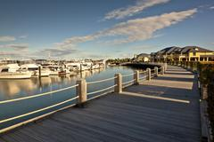 Beautiful wooden pathway in front of a marina - stock photo