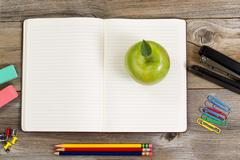Top view of green apple, open notepad surrounded with supplies on rustic wood Stock Photos