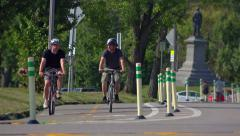 Two Guys Ride Bicycles in Bike Lane in Pittsburgh Stock Footage