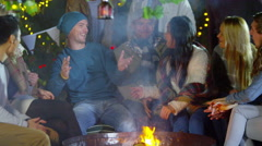 4K Happy mixed ethnicity friends socializing outdoors in front of fire pit Stock Footage