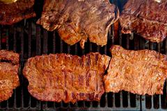 Beef meat barbecue grilled with embers and smoke - stock photo
