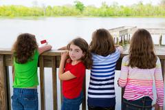 Children girls back looking at lake on railing Stock Photos