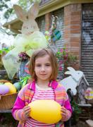 Easter blond girl holding big egg and bunny Kuvituskuvat