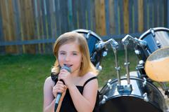 Blond kid girl singing in tha backyard with drums Stock Photos