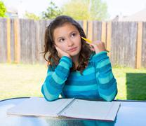 American latin teen girl doing homework on backyard - stock photo