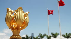 Statue of the Golden Bauhinia with China and Hong Kong flags flying Stock Footage