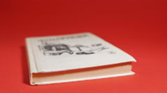 Male hands leafed through an old book lying on a red background. Stock Footage
