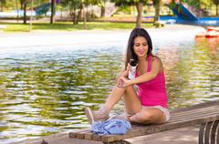 Young beautiful girl sprayinng insect repellent - stock photo