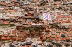 No climbing sign on old insecure wall Stock Photos
