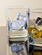 one glass of whiskey and one empty with ice cubes on table with reflection - stock photo