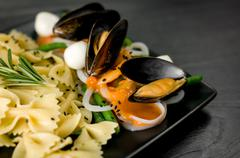 Delicious portion of Farfalle with seafood and mozzarella - stock photo