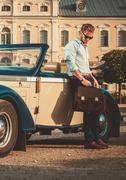 Stock Photo of Confident wealthy young man with briefcase near classic convertible