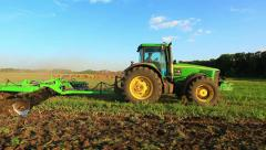 tractor in a field pulls the cultivator - stock footage
