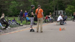 Plastic skaters on one wheel leg slalom and people audience. 4K Stock Footage