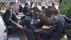 Chinese shoeshine, man smoking cigarette Stock Footage