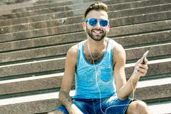 Man listening to the music with earbuds from a smart phone - stock photo