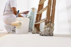 painter man at work with a roller, bucket and scale, bottom view - stock photo