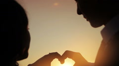 Hands of men and women came together form the symbol of a heart shape at sunset Stock Footage
