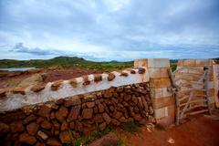 Masonry red stonewall in Menorca with fence door - stock photo