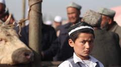 Uighur boy close-up, livestock market, China Stock Footage