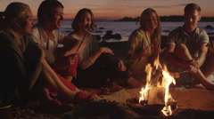 Group of People near Campfire Frying Meat at Night Stock Footage