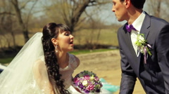 Young beautiful couple bride and groom have fun dancing and singing in the park Stock Footage