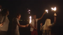 Group of Young Happy People with Sparkling Fireworks in Hands on the Beach - stock footage