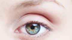 Macro Close-up eye blinking. Young Woman is opening and closing beautiful eye. - stock footage