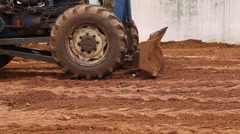 Tractor plows a red soil Stock Footage