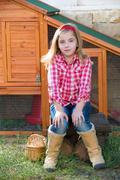 Breeder hens kid girl rancher farmer sitting in chicken tractor Stock Photos