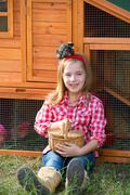 breeder hens kid girl rancher farmer with chicks in chicken coop - stock photo