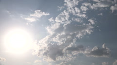 The bright sun shines on blue sky. Over the sky floating clouds. Timelapse. Stock Footage