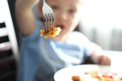 Child while eating. - stock photo