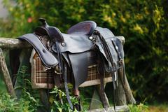 Old ornamental saddle on the wooden fence - stock photo