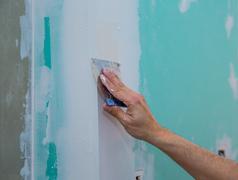 drywall hydrophobic plasterboard trowel plastering seam - stock photo
