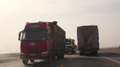 Turphan highway, driving past trucks, China Stock Footage