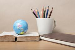 Book and earth ball with color pencil Stock Photos