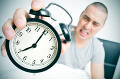 angry young man in bed holds his alarm clock - stock photo