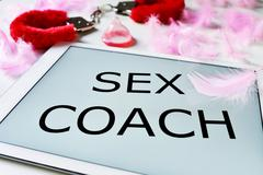 fluffy handcuffs and a tablet computer with the text sex coach - stock photo