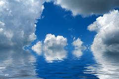 Blue cloudy sky reflecting in water Stock Photos