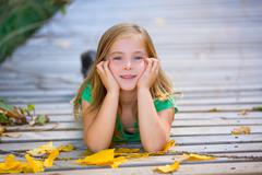 Kid girl in autumn wood deck with yellow leaves outdoor - stock photo