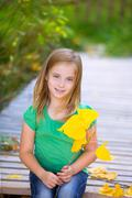 Kid girl in autumn wood deck with yellow leaves outdoor Stock Photos