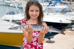 Happy kid fisherwoman with barracuda fish catch - stock photo