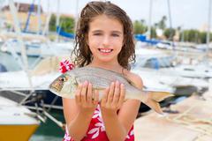 Happy kid fisherwoman with dentex fish catch - stock photo