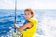 kid girl boat fishing trolling rod reel and yellow life jacket - stock photo