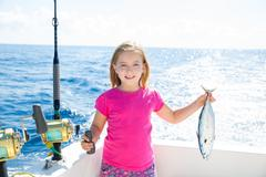 Blond kid girl fishing tuna little tunny happy with catch Stock Photos