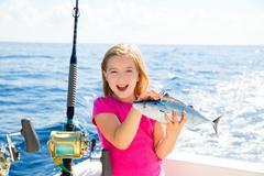 Blond kid girl fishing tuna bonito sarda fish happy catch - stock photo
