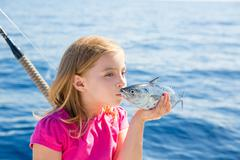 Blond kid girl fishing tuna little tunny kissing for release Stock Photos