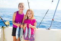 Happy tuna fisherwomen kid girls with fishes catch - stock photo